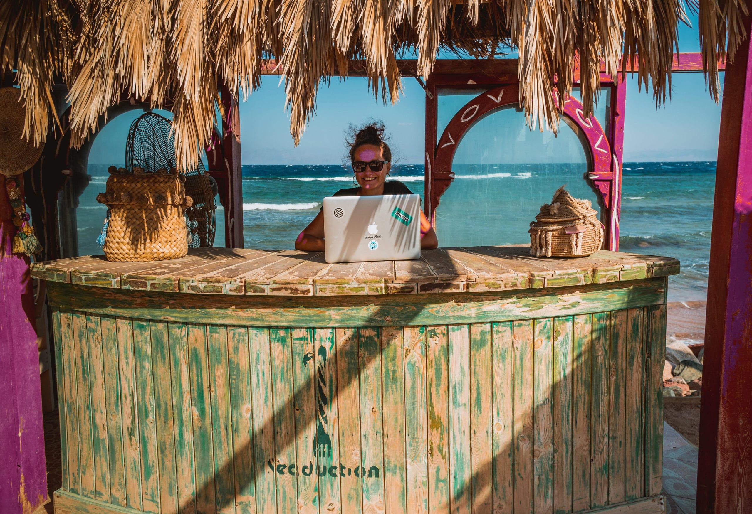 Eine digitale Nomadin arbeitet am Strand.